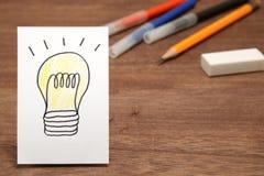在白皮书和文具的电灯泡图画作为背景 免版税图库摄影