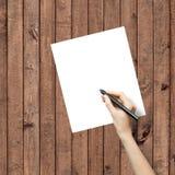 在白皮书板料的手图画 免版税库存照片