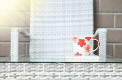 在白皮书的特写镜头逗人喜爱的杯子在被弄脏的木织法桌和椅子上构造了背景 库存图片