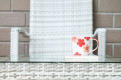 在白皮书的特写镜头逗人喜爱的杯子在被弄脏的木织法桌和椅子上构造了背景 免版税库存图片