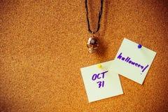在白皮书笔记,在黄柏板的别针的紫色手写与黄色和紫色别针,作为背景的金属头骨下垂项链 免版税库存照片