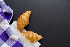 在白皮书袋子的鲜美新月形面包 黑背景用甜点心 顶视图 平的位置 复制文本的空间 免版税库存照片