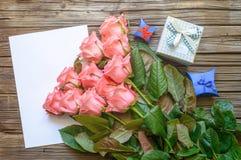 在白纸的桃红色玫瑰与礼物盒 免版税图库摄影