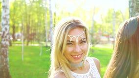 在白肤金发和深色的妇女的太阳光芒相似的服装的在被日光照射了公园跳舞 影视素材