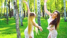 在白肤金发和深色的妇女的太阳光芒跳舞在被日光照射了公园的相似的服装的 影视素材