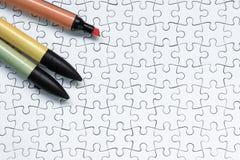 在白色七巧板背景的五颜六色的记号笔 免版税库存照片