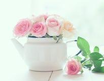 在白色上釉的葡萄酒茶壶的玫瑰 免版税库存照片