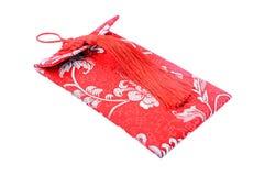 在白色与中国织品设计的小红色袋子隔绝的 库存照片