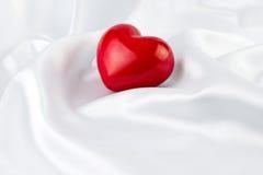 在白色丝绸的红色心脏 免版税库存图片