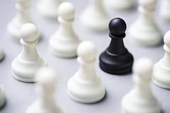 在白色中的黑棋子一个 库存图片