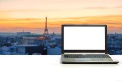在白色书桌上的膝上型计算机有被弄脏的埃佛尔铁塔的在sunse的巴黎 库存图片