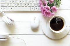 在白色书桌和计算机上的顶视图耳机有一杯文本和咖啡的桃红色花和copyspace区域的在耳机旁边的 图库摄影