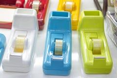 在白色书桌安置的3台多彩多姿的磁带分配器 库存图片