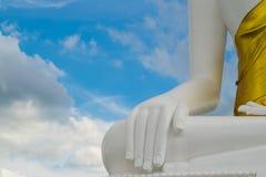 在白色云彩和蓝天b的白色菩萨石头雕塑手 库存照片