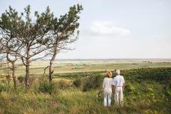 在白色亚麻制礼服的两三个资深成人站立与他们的后面户外,在手上花束  免版税库存照片