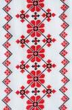 在白色亚麻布的元素手工制造刺绣由红色和黑棉花螺纹 免版税图库摄影