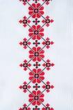 在白色亚麻布的元素手工制造刺绣由红色和黑棉花螺纹 免版税库存照片