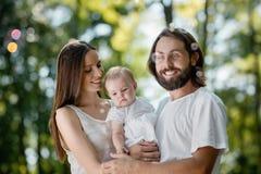 在白色便服和那里小女婴打扮的母亲、父亲是在公园和看肥皂 免版税图库摄影