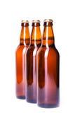 在白色冰冷的啤酒隔绝的三个瓶 库存照片