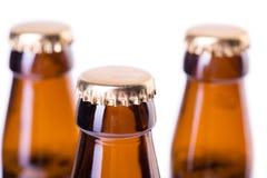 在白色冰冷的啤酒隔绝的三个瓶 免版税库存图片
