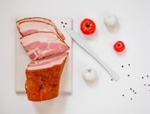 在白色切板的熏制的烟肉 免版税图库摄影