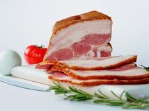 在白色切板的熏制的烟肉 免版税库存图片