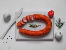 在白色切板的熏制的香肠 免版税图库摄影