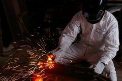 在白色制服的建筑焊工有与火花的防护盔甲焊接钢的在车间 产业工人概念 库存图片