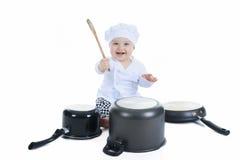 在白色前面的逗人喜爱的矮小的厨师男孩 免版税库存照片