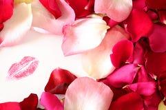 在白色卡片的红色妇女嘴唇标记在玫瑰花瓣中 免版税库存图片