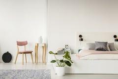 在白色卧室内部的桃红色木椅子与在b旁边的植物 免版税库存照片