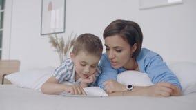 在白色卧室,妈妈和儿子看看片剂屏幕和笑 在床上早晨读书的幸福家庭 股票录像