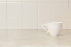 在白色厨房用桌上的陶瓷茶杯 库存照片