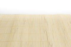 在白色厨房用桌背景的布朗竹席子 库存照片