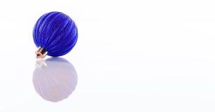 在白色反射性有机玻璃背景隔绝的一个蓝色圣诞节球 免版税图库摄影