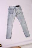 在白色后面地面的蓝色牛仔裤 免版税库存图片