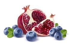 在白色后面隔绝的石榴半,四分之一和蓝莓 免版税库存图片