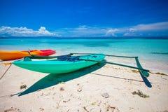 在白色含沙热带海滩和turquiose海洋的小船 库存照片
