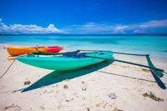 在白色含沙热带海滩和turquiose海洋的小船 免版税库存照片