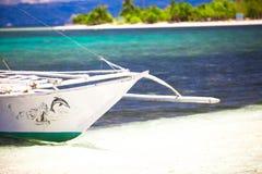 在白色含沙热带海滩的小船 免版税库存图片