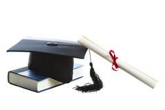 在白色和书隔绝的毕业帽子、文凭 免版税库存图片