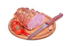 在白色和刀子隔绝的猪肉火腿、蕃茄、胡椒、大蒜 免版税库存照片