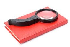 在白色和放大镜查出的书 免版税库存图片