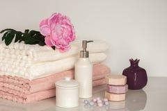 在白色和桃红色颜色的巴恩设置 毛巾,芳香油,花,肥皂 选择聚焦,水平 免版税库存图片