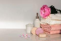 在白色和桃红色颜色的巴恩设置 毛巾,芳香油,花,肥皂 选择聚焦,水平 库存图片