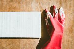 在白色和棕色木的肮脏的红色手套 免版税图库摄影
