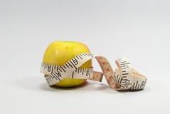 在白色和测量的磁带隔绝的苹果计算机 图库摄影