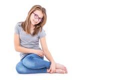在白色和灰色T恤杉的年轻青春期前的女孩隔绝的蓝色牛仔裤 免版税库存照片