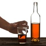在白色和瓶白兰地酒隔绝的玻璃 免版税库存图片