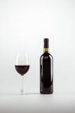 在白色和瓶的红葡萄酒隔绝的玻璃 库存照片